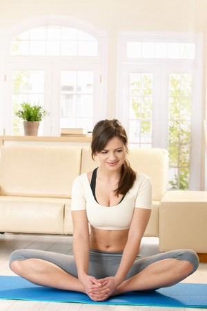 Young woman exercising on blue floor mat in bright living room, smiling. Stock Photo - 7723672