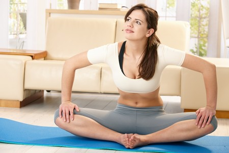 Girl doing stretching exercise at home, sitting on blue polyfoam mat, hands pushing knees. photo