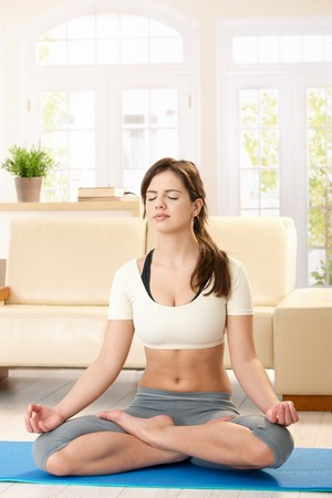 Girl meditating in lotus posture with closed eyes in sunlit living room. photo