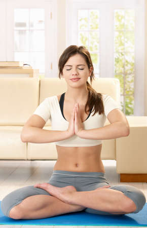 Smiling young woman meditating on blue floor mat in living room with closed eyes. photo