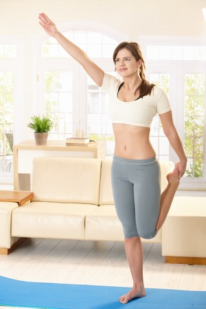 Pretty girl doing exercise in living room, standing on blue floor mat, holding foot, arm raised. photo