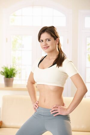 straddle: Sporty girl looking at camera confidently, standing in straddle with hands on hip. Stock Photo
