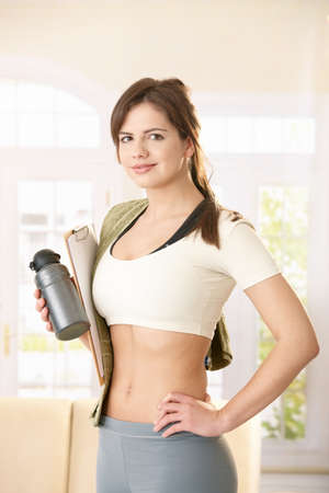 Girl going to gym with towel, gourd and clipboard in hand, smiling at camera confidently. photo