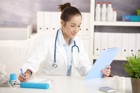 Young female doctor working in office, sitting at desk doing paperwork.  photo