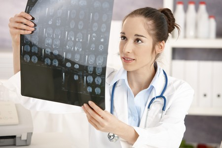 Young female doctor sitting at desk in doctors room looking at x-ray image. Stock Photo