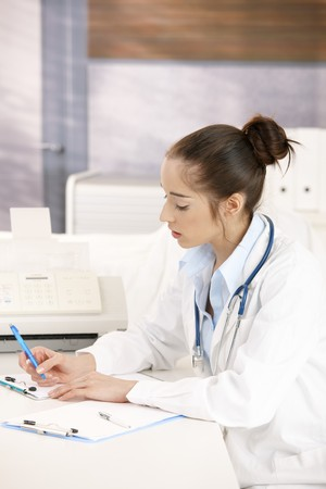Young female doctor working at desk in doctors room writing. photo