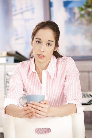 Portrait of young woman drinking coffee in bright office, looking at camera, holding mug. photo
