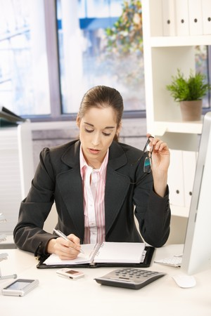 Businesswoman taking notes into organizer, sitting at desk in bright office holding glasses. photo