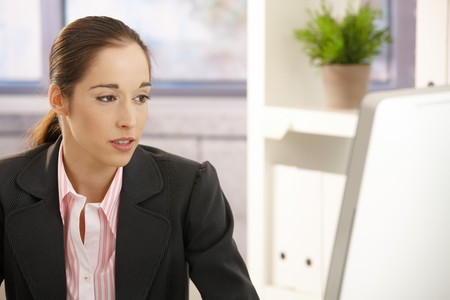 Young businesswoman sitting in office looking at screen. photo