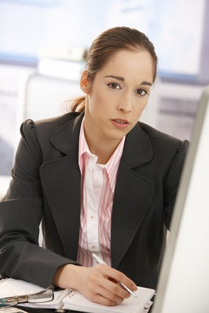 Young businesswoman sitting at desk, working, looking at camera. photo