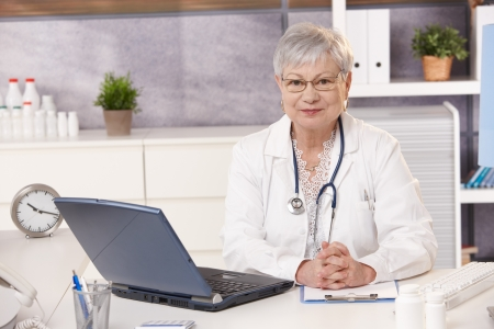 Portrait of senior doctor at work, looking at camera, sitting at desk. photo