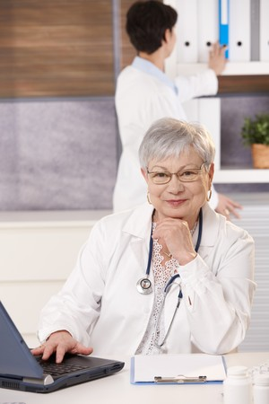 Senior doctor sitting at desk with laptop, smiling at camera, assistant looking at folder in background. photo