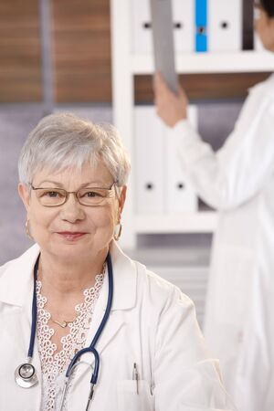 Portrait of senior doctor sitting in office looking at camera, assistant using folder in background. photo