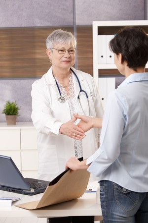 Senior doctor meeting patient in office, shaking hands, patient holding x-ray image in envelope. Stock Photo - 7653564