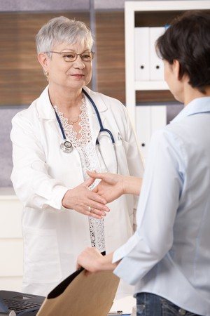 Senior doctor greeting patient in office, smiling, patient holding scan result. photo