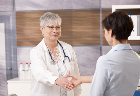 consultant physicians: Senior doctor shaking hand with patient in office.