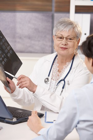 Senior doctor showing scan results to patient in office. photo