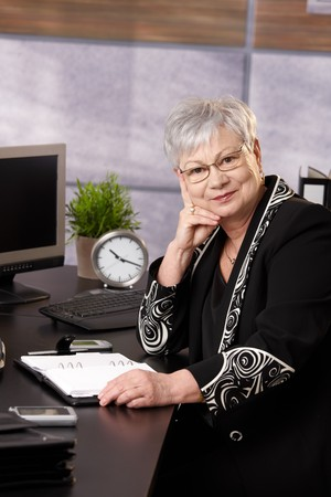 older women: Senior businesswoman sitting at desk in office, looking at camera, smiling.
