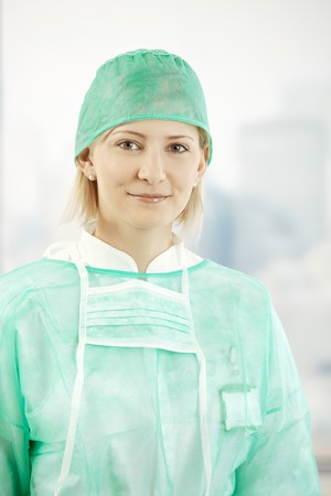Portrait of female medical doctor wearing scrub suit, smiling at camera. photo