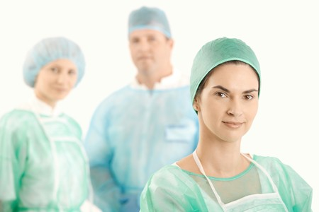 female surgeon: Smiling doctor in scrubs with medical crew in background. Stock Photo