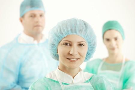 guanti infermiera: Equipe medica in uniforme, femmina medico sorridere alla telecamera, i colleghi in background.