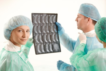 Medical team examining x-ray image, female doctor smiling at camera. Stock Photo - 7653596