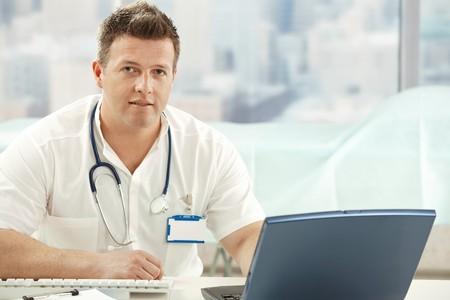 uniformes de oficina: Mid-Adult m�dico sentado en el escritorio en la Oficina mirando la c�mara.