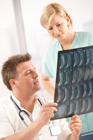 Mid adult handsome doctor examining x-ray image with nurse in office. Stock Photo - 7653633