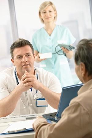 blood pressure gauge: Mid-adult medical doctor talking to elderly patient, nurse holding blood pressure gauge in background.