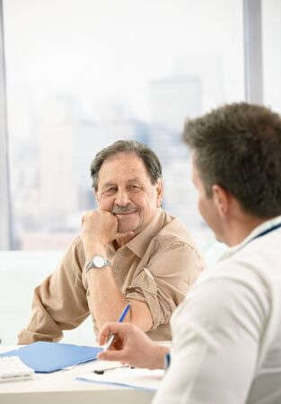 color consultation: Smiling elderly patient sitting at doctors office on consultation. Stock Photo