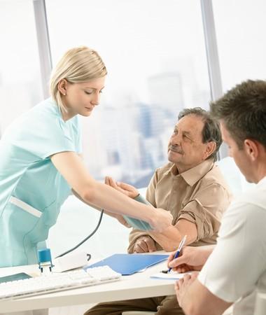 taking note: Infermiere di misurare la pressione sanguigna dei vecchi paziente, medico prendendo note alla scrivania.  Archivio Fotografico