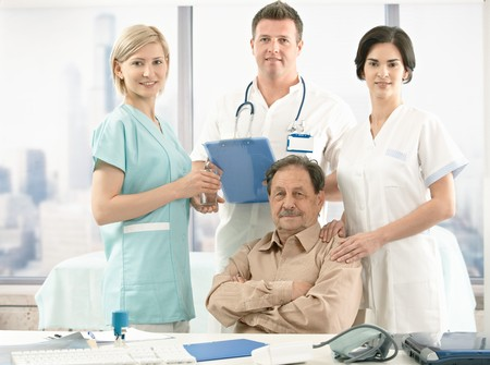 Portrait of senior patient sitting at desk, medical team around, smiling at camera. photo
