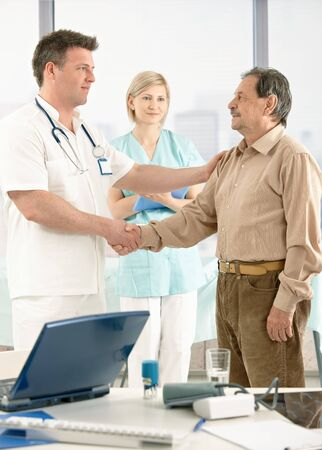 Smiling medical doctor congratulating senior patient on successful recovery, nurse in background. Stock Photo - 7653635