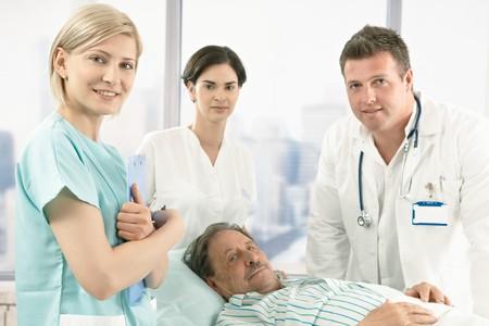 personal medico: Antiguo paciente var�n mentir en la cama de hospital, vistiendo el pijama, equipo m�dico, sonriente en la c�mara.