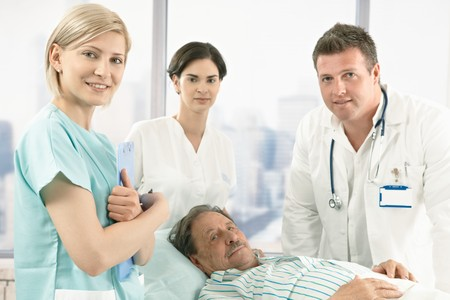 Old male patient lying in hospital bed wearing pyjama, medical team around, smiling at camera.