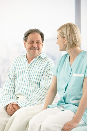 Senior patient in hospital, sitting on bed, chatting to nurse. Stock Photo - 7653603