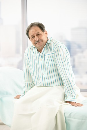 Portrait of old male patient sitting on hospital bed, wearing pyjama, smiling at camera. photo