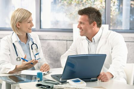 consultant physicians: Two medical doctors consulting, smiling at office desk.