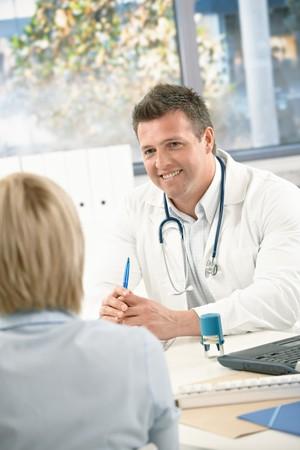 medico con paciente: Sonriendo a paciente de consultor�a de doctor en medicina en Oficina brillante.  Foto de archivo