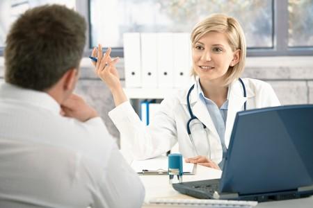 Doctor patient: Seguro m�dico femenina discutiendo de diagn�stico con el paciente en una Oficina, sonriendo.