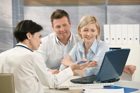 pacientes: Doctor en medicina, mostrando los resultados a los pacientes en los equipos de oficina.