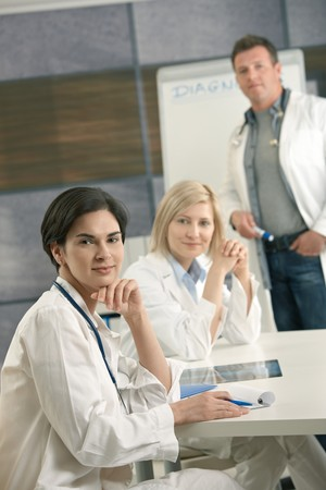 Portrait of medical team consulting in office, doctors smiling at camera. Stock Photo - 7653608