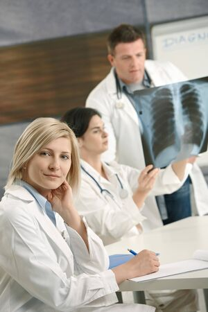 Smiling female medical doctor looking at camera, doctors consulting diagnosis of x-ray image in background. Stock Photo - 7653626