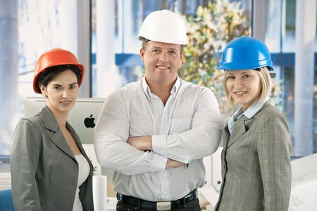 Confident professionals wearing hardhat posing in office together, smiling. photo