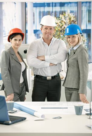 Architects standing in office at desk wearing hardhat, smiling at camera. Stock Photo - 7653639