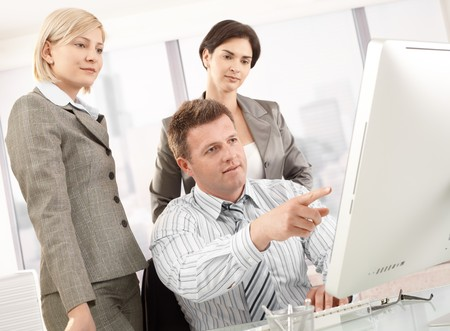 looking at computer screen: Business team in office, businessman pointing at computer, businesswomen looking at screen.