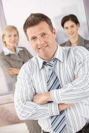 Confident businesspeople standing with arms folded in office, smiling. Stock Photo - 7653650