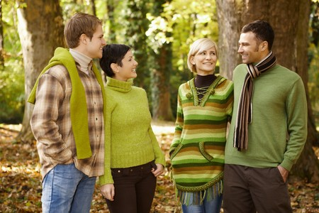 two friends talking: Two smiling couples talking in autumn forest. Stock Photo