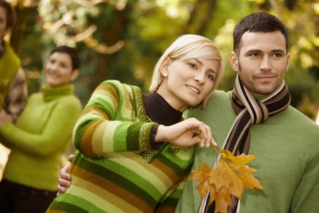 Closeup portrait of young couple embracing in autumn park, woman holding leaves. photo