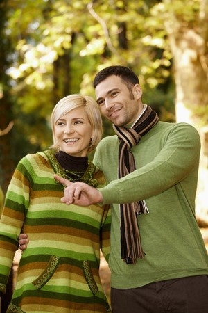 Happy couple on autumn walk in park, man showing something to smiling woman. photo